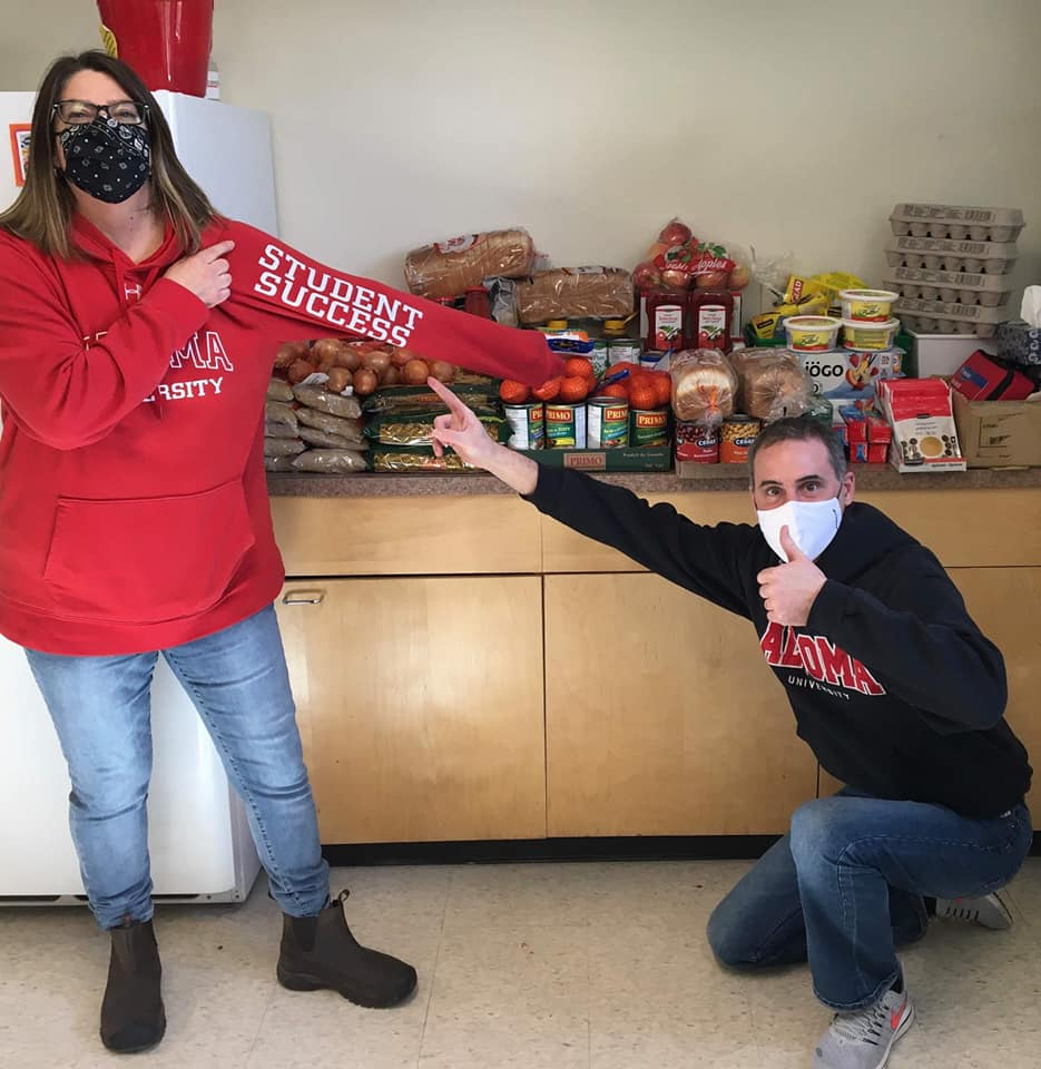 two staff members infront of a counter of food